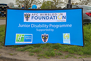 AFC Wimbledon foundation - junior disability sign during the EFL Sky Bet League 1 match between AFC Wimbledon and Accrington Stanley at the Cherry Red Records Stadium, Kingston, England on 6 April 2019.