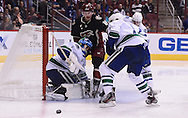 Nov 5, 2013; Glendale, AZ, USA; Vancouver Canucks goalie Roberto Luongo (1) blocks the puck against the Phoenix Coyotes forward Shane Doan (19) in the second period at Jobing.com Arena. Mandatory Credit: Jennifer Stewart-USA TODAY Sports