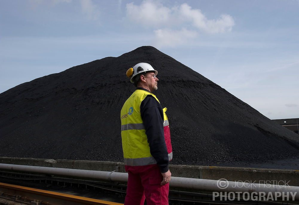 An employee stands next to a mountain of coal at the Essent Energie power station, in Geertruidenberg, Netherlands, on Monday March 22, 2010. Essent Energie is owned by RWE AG. (Photo © Jock Fistick).