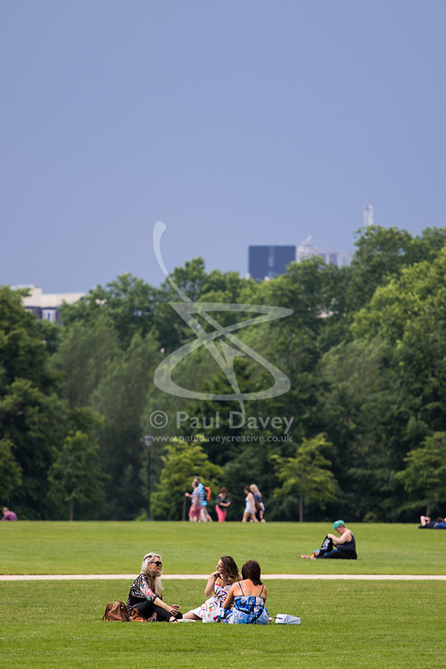 London, June 2nd 2017.  Friends relax during lunch hour in Hyde Park as clouds build up ahead of forecast thunderstorms.