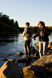 A couple fly-fishing on the Moose River below the dam on Brassua Lake in Rockwood, Maine.  Moosehead Lake region.