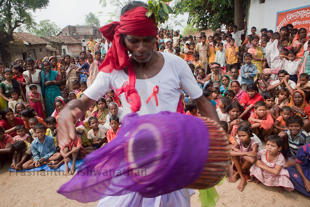 Hensla Village, Arsa Block, Purulia District, West Bengal, India. 30 September 2011: Villagers react as they watch a HIV/AIDS awareness generating  folk dance organized by the Red Ribbon Club ( RRC) and Link workers at Hensla Village. The objective of RRC is to empower youth through information regarding HIV/AIDS prevention, care and support and tretment. RRC is working in close co-ordination with LW's and Link voulenteers.  The Link Worker Scheme (LWS) proposed under the National Aids Control Programme iii has been designed specifically to address populations with high-risk behaviours. UNICEF supports implementation of this scheme in 26 districts spread out in 10 states. In Purulia LWS covers 99 villages with 52 link workers reach out to these villages.  UNICEF India/2011/Vishwanathan