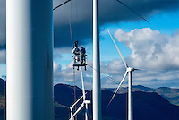Workers hang from bucket to service blades of wind turbines in Kodiak, Alaska