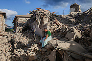 24 August 2016, Amatrice Italy - A man survived the earthquake sits on the rubble in front of his house completely destroyed by the earthquake.