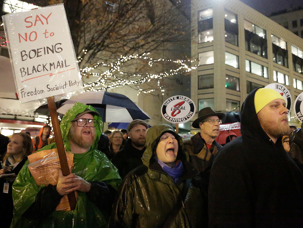 Supporters stand in the rain at a rally organized by the Washington State Labor Council to show support for Machinists union members at Westlake Park in Seattle, Washington November 18, 2013. The International Association of Machinists and Aerospace Workers union rejected a contract offer Wednesday that Boeing said was necessary for the new 777 jetliner to be built in Washington.