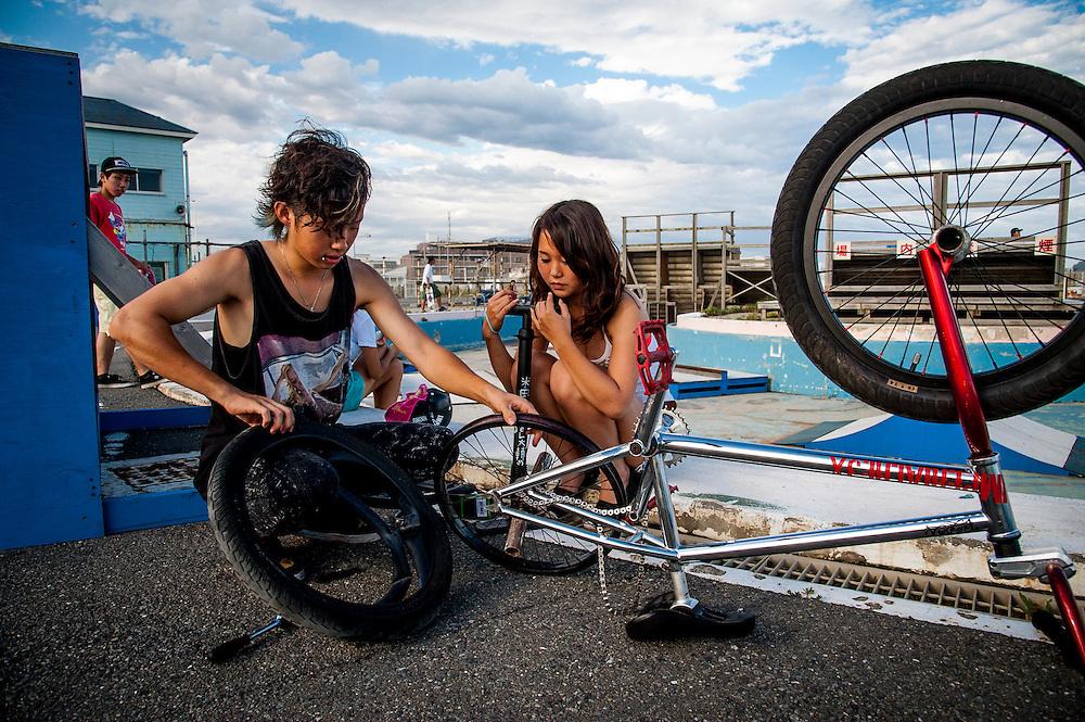 A boy fixes his BMX bike while his girlfriend watches. Shonan Beach in Fujisawa, Kanagawa Prefecture, 50 kilometers south of Tokyo.