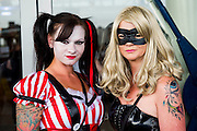 Dee Cable (L), 33, comes as Harlequin from Batman. She was encouraged to dress up by her friend, Emma Thair-White, 42 , who plays canary from sc-fi show Arrow.  Both travelled in from essex for the day. London Film and Comic Con 2014, (LFCC), at Earls Court, London, UK.