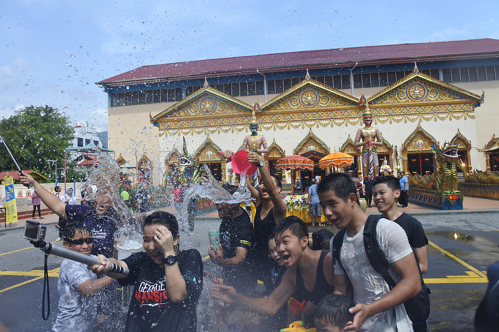 People trying to take a selfie at the Songkran festival with water being thrown at them