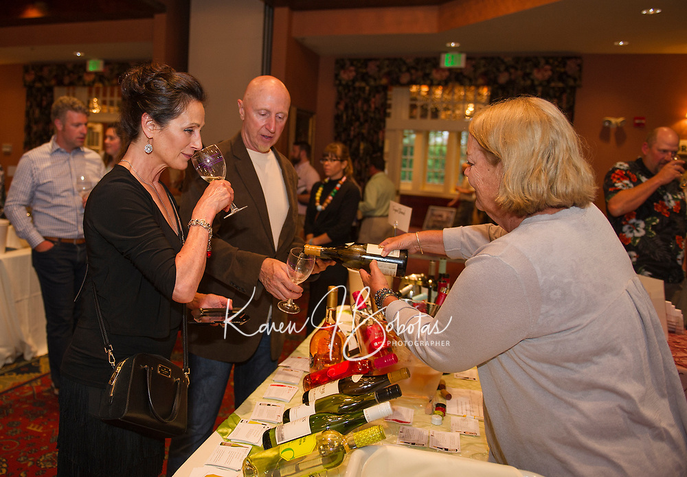 Kimberly Robinson from Vineyard Blends pours a tasting of Vouvray for Janis and Mike Lago during the Winnipesaukee Wine Festival at Church Landing Thursday evening.  (Karen Bobotas/for the Laconia Daily Sun)