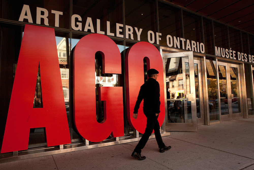 A man walks by the graphic sign at the entrance to the Art Gallery of Ontario.