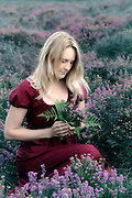 a woman in a red dress is sitting in the heather with a bouquet of flowers