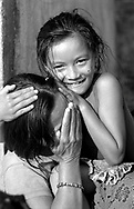 A young girl has fun while her mum doesn't feel comfortable in front of the camera.