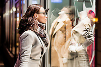 Portrait of young attractive woman looking at the dress on a manequin in shop through the window