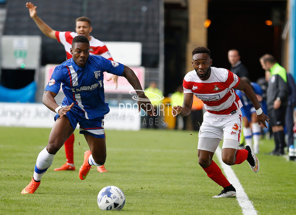 Cedric Evina breaks free down the line, dismissing Ryan Jackson's attempt to stop him during the Sky Bet League 1 match between Gillingham and Doncaster Rovers at the MEMS Priestfield Stadium, Gillingham, England on 5 September 2015. Photo by Andy Walter.