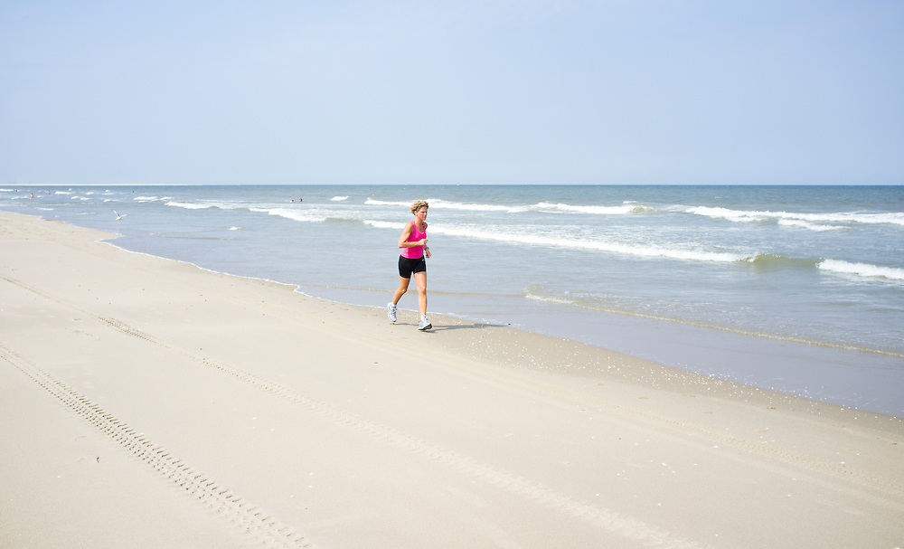 Nederland. Den Haag, 12 juli 2011.<br /> Vrouw op strand Kijkduin, hardlopend. Recreatie; recreeren; leisure; holiday; vakantie; vrije tijd; vrij; vrijheid; ferien; freizeit; sport; sporten; run; running; jogging; joggen; hardlopen; rennen; conditie; ontspanning; gezondheid; strand; beach, sporting, lichamelijke gezondheid, <br /> Foto Martijn Beekman
