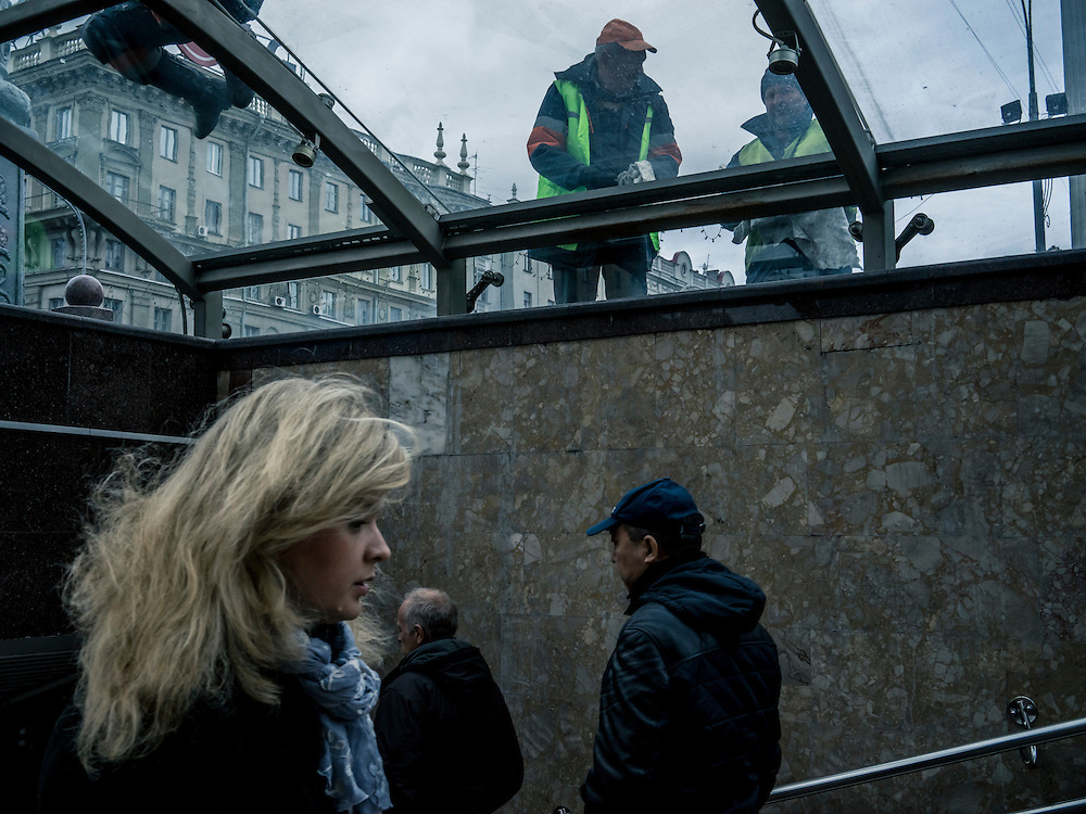 Workers clean the glass covering of a stairway on Friday, October 9, 2015 in Minsk, Belarus. More than 70% of the economy in Belarus is state-run, creating a ready base of support for President Alexander Lukashenko, who is certain to be re-elected to a fifth term on Sunday.