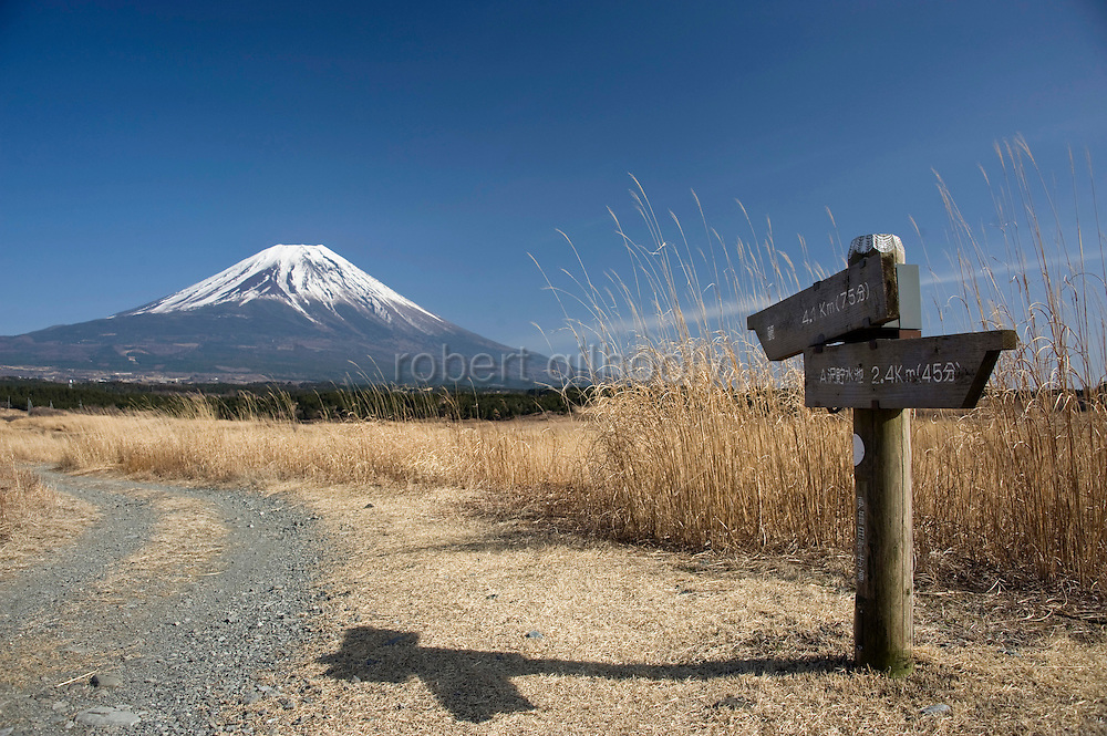 Mt Fuji can be seen behind a signpost along a walk that takes trekkers through parts of the Asagiri Plateau in Shizuoka Prefecture Japan on 22 March 2013.  Photographer: Robert Gilhooly