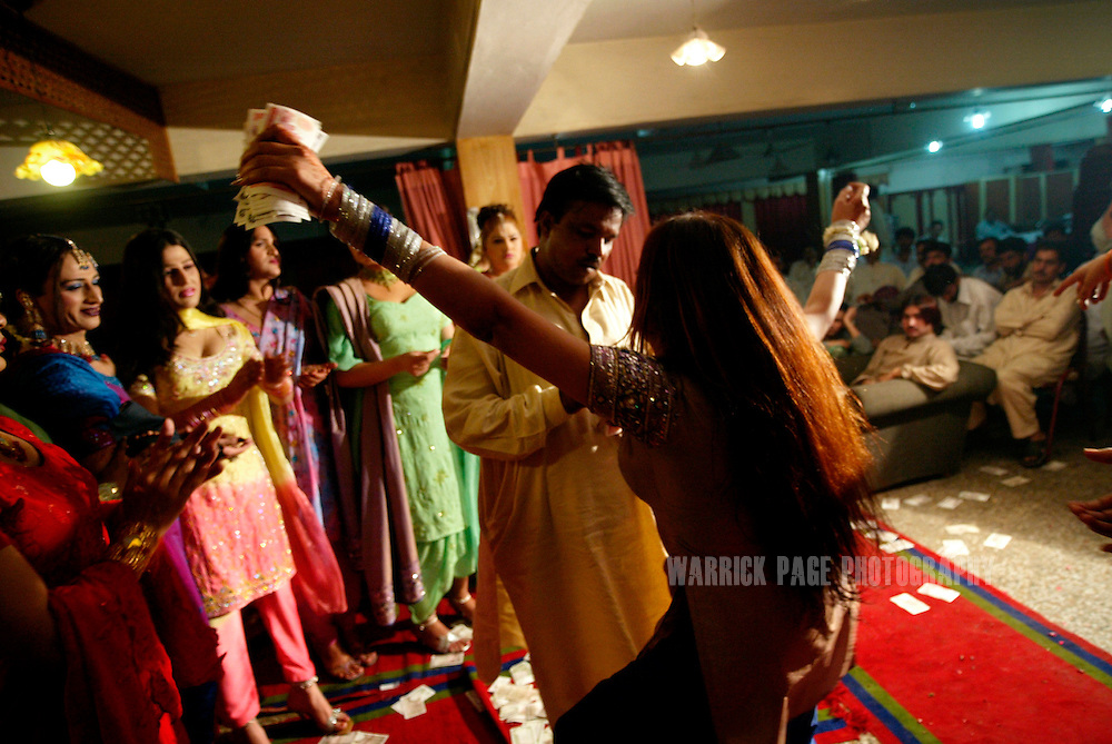 "A man stuffs money into the bra of a hijra (eunuch), during a performance at an underground party, June 16, 2005, Rawalpindi, Pakistan. The suspected hideout of Osama Bin Laden, Al Qaeda leaders and countless Islamic militants, Pakistan is also home to one of the subcontinents largest communities of transsexuals, eunuchs and transvestites, or as they are more commonly known - Hijras. Caught between modernity and fundamentalism at the frontline in the war against terror, the Islamic Republic is a country at war with its own identity, yet its Kushras (Urdu for eunuch) stand out as a tight-nit community of devout Muslims. As Pakistan's most marginalised community, they live in fear ""24 hours a day"", according to the group She-male Rights of Pakistan. Hijras are considered by many as unclean, amoral, drug users, and who also have the ability to place curses. Many people fear their curse so gravely, they will give generously when a Kushra comes to beg in their neighbourhood and ask them for Allah's blessing.. (Photo by Warrick Page)"