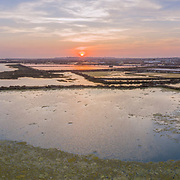 Sunset aerial panoramic seascape view of Olhao salt marsh Inlet, waterfront to Ria Formosa natural park. Algarve. Portugal.