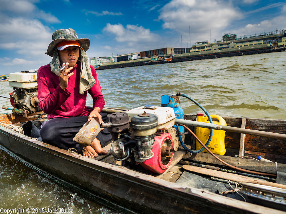 14 OCTOBER 2015 - BANGKOK, THAILAND:  A spotter bails water out his boat while the diver he works with is on the bottom of the Chao Phraya River in Bangkok. Divers work in two man teams on small boats in the Chao Phraya River. One person stays in the boat while the diver scours the river bottom for anything that can be salvaged and resold. The divers usually work close to shore because the center of the river is a busy commercial waterway with passenger boats and commercial freight barges passing up and down the river all day long. The Chao Phraya is a dangerous river to dive in. It's deep, has large tidal fluctuations, is fast flowing and badly polluted. The divers make money only when they sell something.   PHOTO BY JACK KURTZ