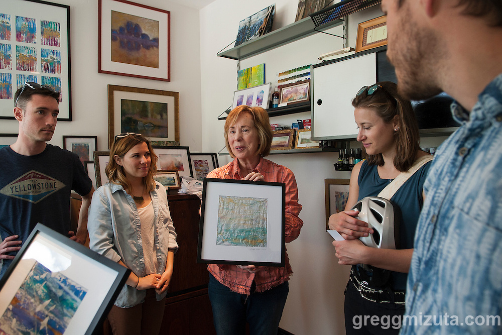Artist Sara Hill explains one of her painting on rice paper to the ST(r)EAM Bike/Art tour group at her studio. Sara's studio was one of the venues on Jodi Eichelberger's ST(r)EAM Bike/Art tour through the Surel Mitchell Live-Work-Create District in Garden City, Idaho on April 30, 2016.<br /> <br /> Artists and venues on the tour included Surel's Place, Megan Levad, Sara Hill, Will Bennett, Victor Myers and Corridor Surf Shop, Geoffery Krueger, Karen Woods, Gina Phillips, Hindi Morland, Heidi Haislmaier and the new Telaya Winery where Segreto Wood Fired Pizza set up shop for the bike tour group.