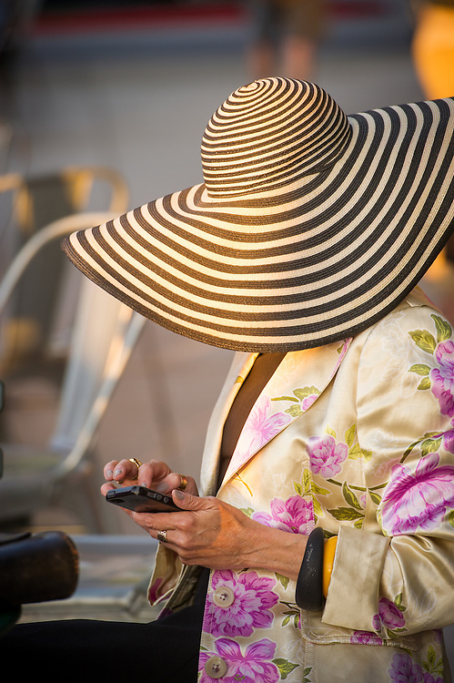 Woman typing into smart phone, wearing a large hat in Baltimore, Maryland, USA