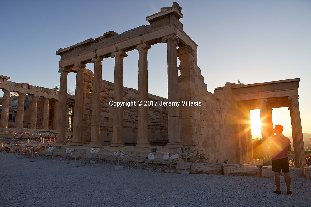 The entrance of the Erechtheion, lined with six long Ionic columns during sunset.<br />