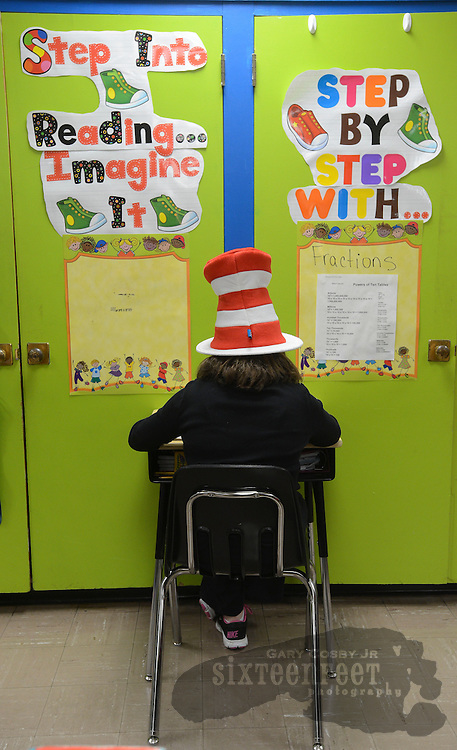 Photo by Gary Cosby Jr.    Eastwood Elementary in Decatur celebrated Dr. Seuss Day Thursday in honor of the legendary children's author's birthday.  Jenna Russell sits in her fifth grade class and takes a test in her Cat In The Hat hat.