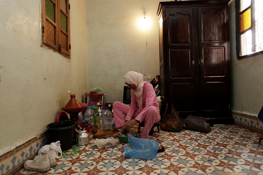 Saida 32 years old, a single mother cooks a tagine in the kitchen area of the only room of 12 square meters  where she lives, Daoudiat district - Marrakech 28 April 2013