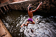 27th September, 2014, Mehrauli, India. A boy jumps into Gandhak Ki Baoli in Mehrauli,on the 27th September, 2014, Delhi, India<br /> <br /> At the turn of the last century, Delhi had more than 100 baolis, today, many of them have caved in or dried up owing to the declining water table. The number has shrunk to about 15, according to the ASI (Acheological Survey of India). Stepwells (Baolis) are examples of the many types of storage and irrigation tanks that were developed in India, mainly to cope with seasonal fluctuations in water availability. <br /> <br /> PHOTOGRAPH BY AND COPYRIGHT OF SIMON DE TREY-WHITE a photographer in Delhi<br /> <br /> + 91 98103 99809<br /> email: simon@simondetreywhite.com
