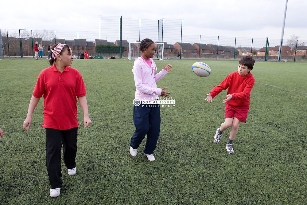 Group of children practicing playing rugby on a playing field at their local leisure centre,