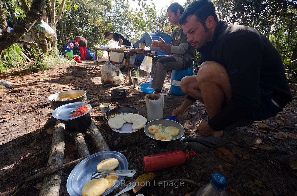 """AUYANTEPUY, VENEZUELA. Guías preparando arepas para el  desayuno en el campamento ''campo lecho''. El Auyantepuy es el mayor de los tepuis del Parque Nacional Canaima. En sus 700 kms2 alberga el salto angel o conocido por lengua indígena Pemon como """"Kerepacupai Vena; es la caída de agua más grande del mundo con sus 979 metros de altura. (Ramon lepage /Orinoquiaphoto/LatinContent/Getty Images)"""