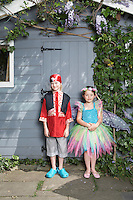 Portrait of young boy (7-9) in pirate costume girl (5-6) in fairy costume by shed