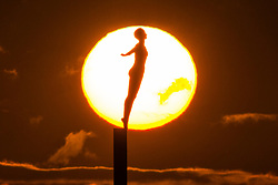 © Licensed to London News Pictures. 10/11/2017. Scarborough UK. The sun rises this morning behind the Diving Belle sculpture at Vincent pier in Scarborough, North Yorkshire. Photo credit: Andrew McCaren/LNP