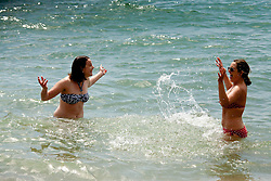 © under license to London News Pictures. 21/07/12. As temperatures rise this weekend, two young women have fun in the water and enjoy a rare break in the wet weather on Brighton beach. Xavier Itter/LNP