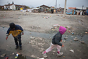 Children are walking the area of Konik Camp located in the suburbs of the city of Podgorica, Montenegro. A huge fire in 2012 detroyed a big part of the refugee camp and many of the inhabitants are living in containers. The housing pictured belongs still to the part with old housing facilities.