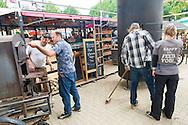 Nederland, Nijmegen, 20160708.<br /> De verschillende houtovens worden in gereedheid gebracht.<br /> Cultureel festival De Kaaij onder de Waalbrug in Nijmegen.<br /> De Kaaij betekent een zomer lang genieten van oude en nieuwe bekenden, muzikanten, theatermakers, chef-koks, dichters, dj's, kunstenaars, venters, bands, stands en entertainers van divers pluimage.<br /> <br /> Netherlands, Nijmegen<br /> The cultural festival The Kaaij under the Waal bridge at Nijmegen.