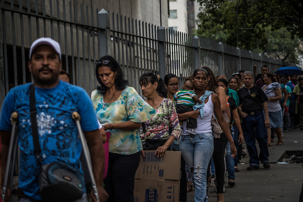 CARACAS, VENEZUELA - JANUARY 15, 2015: Hundreds of people wait in line to enter a  privately owned supermarket that had just received a shipment of milk. Despite being a petro-state with one of the largest oil reserves in the world, basic food goods such as cooking oil, milk, chicken, coffee, rice, sugar and corn meal are difficult to find in stores across Venezuela.