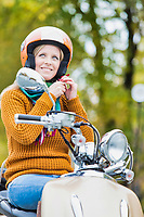 Portrait of mature beautiful woman putting her helmet on to ride motorbike in park