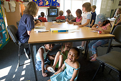 Group of children at Nursery School; some watching a television programme; other sitting under a table laughing,