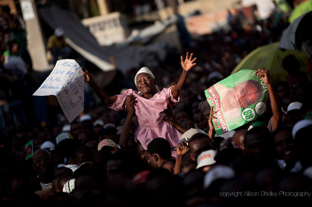 A woman is held above the crowd as Haitian presidential candidate Mirlande Manigat holds a campaign rally, February 18, 2011 in Port-au-Prince, Haiti.