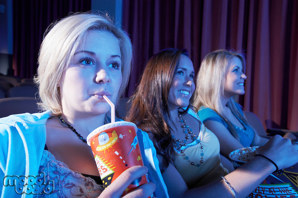 Young woman drinking soft drink sitting with Friends Watching Movie in theatre