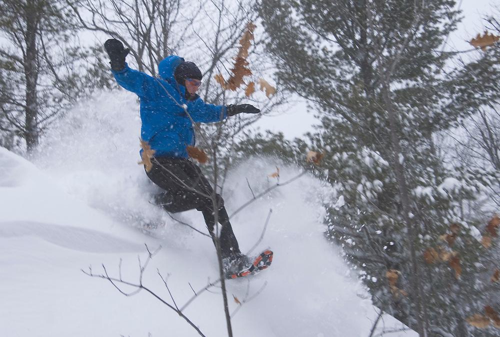 A snowshoer runs through deep powder deep in the woods north of Ishpeming, Michigan.
