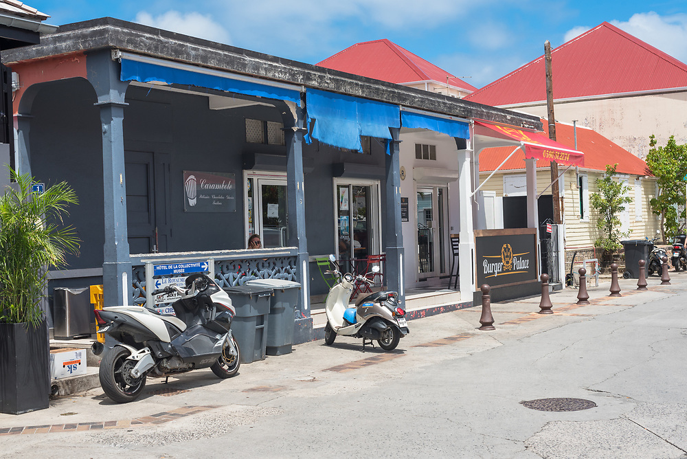 Gustavia, St Barths-- April 25, 2018. Two motorbikes are parked outside a casual restaurant on a Gustavia side street. Editorial Use Only.