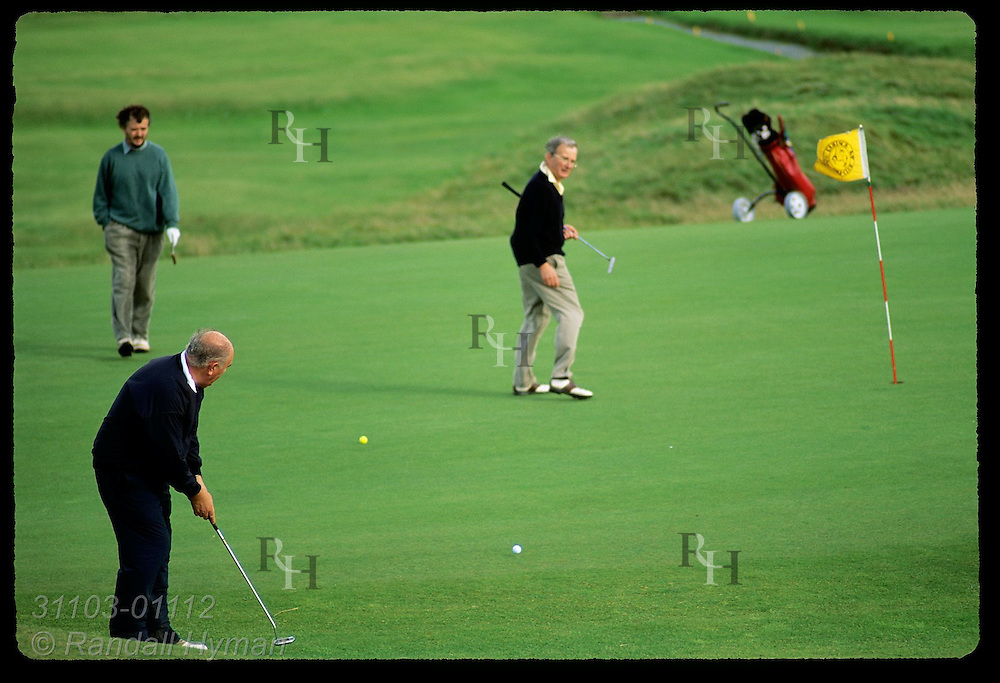 Golfer putts on green as companions watch; Lahinch Golf Course, County Clare, Ireland.