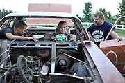 Taylor Krieter, center, family friend Dillon Meadows, left, of Lowell, and Taylor's father Kevin Krieter, prepare her car for Taylor's first demolition derby at the Krieter home in Crown Point earlier this month. ..