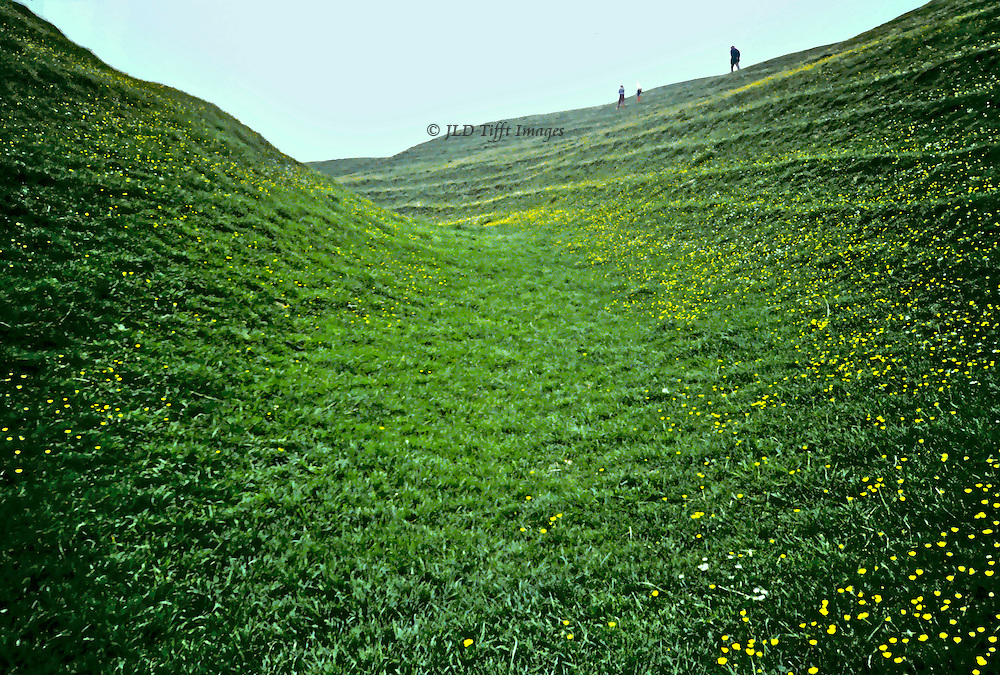 Grass-covered chalk ditch studded with buttercups surrounds the stone circle at Avebury; figures of three distant walkers seen from the bottom of the ditch which is 20 ft deep and 1396 ft in diameter.  Stark contrast between massive ditch and tiny human figures.  Earthworks dated 2500 BC