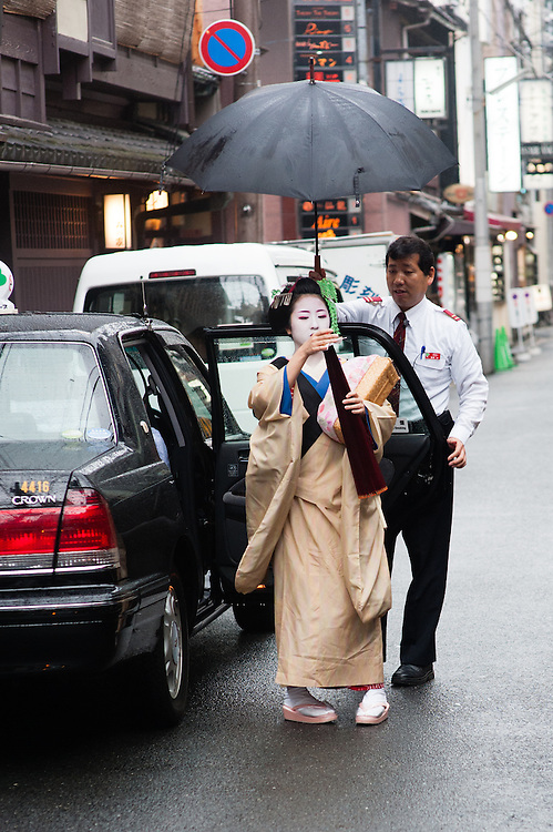Geisha under umbrella about to get into black cab in Gion district (Kyoto, Japan)