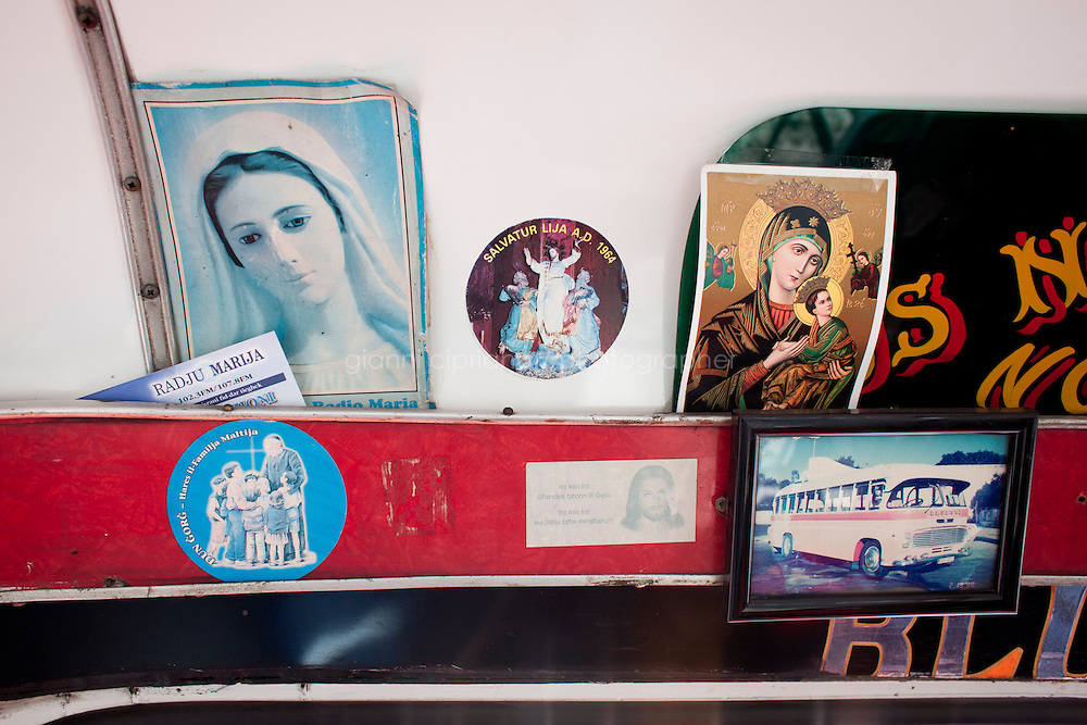 25 February 2011. Valletta, Malta. A detail of the interior of Frankie Vella's Leyland n. 74 bus shows a picture of his bus, as well as religious cards and stickers. These buses, some of which are 60 years old, will be replaced in the following months by newer buses. There are approximately 500 buses in public transit service in Malta. The drivers themselves own most of the buses, but operate to a unified timetable set by the transport authority.<br /> <br /> <br /> &copy;2011 Gianni Cipriano<br /> cell. +1 646 465 2168 (USA)<br /> cell. +39 328 567 7923<br /> gianni@giannicipriano.com<br /> www.giannicipriano.com