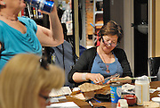 Canada, Ontario Windsor, 2016. Artist Trading Card workshop at Ten Thousand Villages is a MayWorks Windsor 2016 event. Lorraine Steel works on her cards.